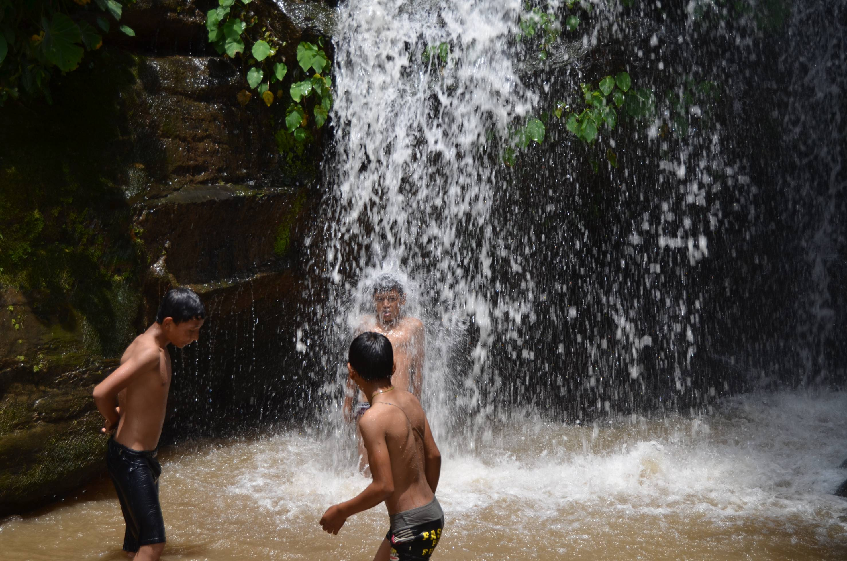 Children beating off the heat and enjoying in the coll waterfall at Nagarkot