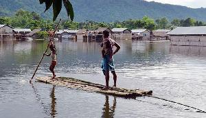 असम के कई हिस्सों में भारी बारिश, बांस की नाव से सड़क पार कर रहे लोग