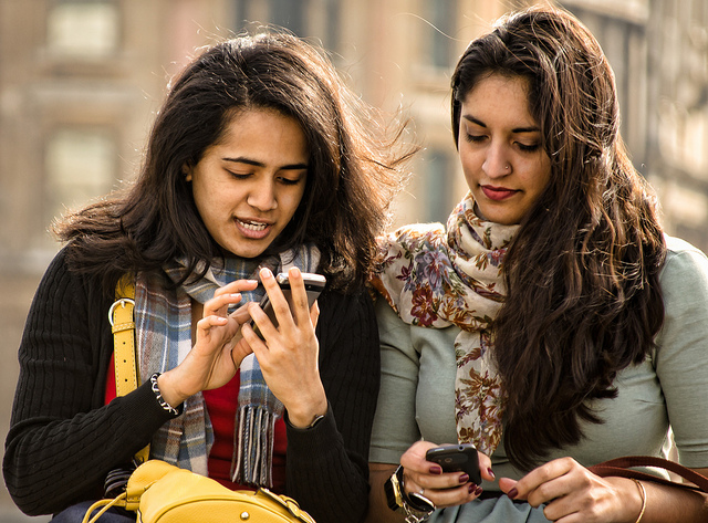 Two young South Asian women friends in sweaters and scarves, looking at their mobile phones