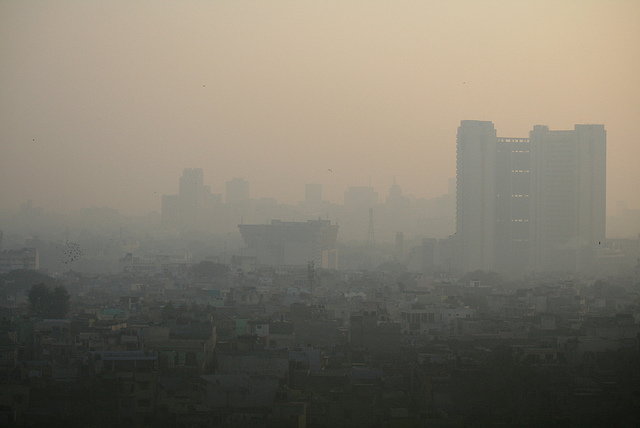 Birds-eye view of the city, with building showing faintly through a thick brown smog