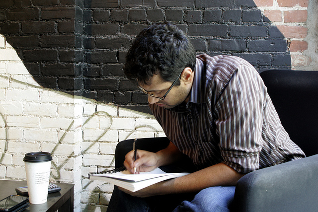 A bespectacled young man writing in a notebook while seated by a coffee table with a cup of coffee on it