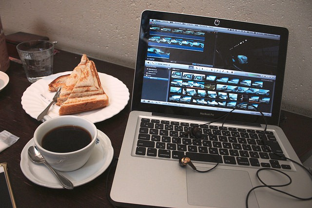 Coffee cup, glass of water and sandwich next to a laptop with a video editing program