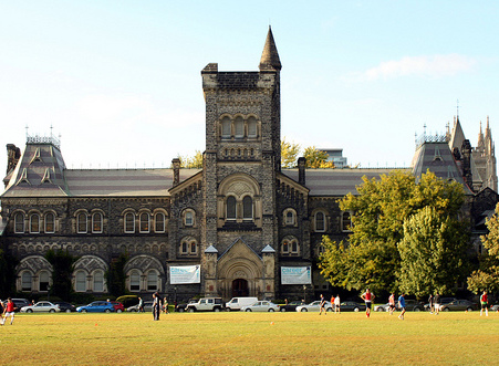 Historic building on University of Toronto campus, with people walking about the lawns on a sunny day
