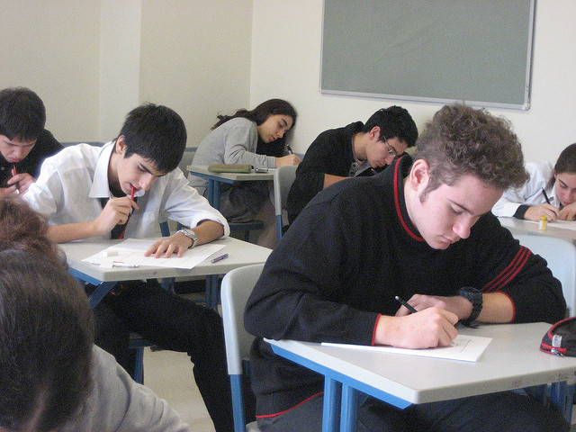 Students in classroom writing an exam