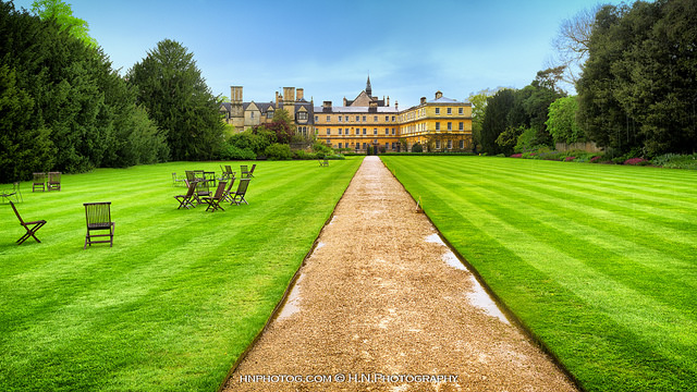 University of Oxford grounds with green grass under a clear blue sky
