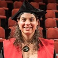 Picture of Cecile Massiot wearing graduation attire and smiling, with auditorium in background