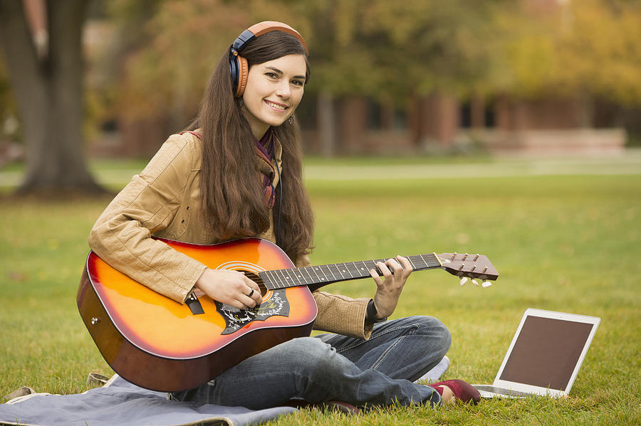 College student playing a guitar