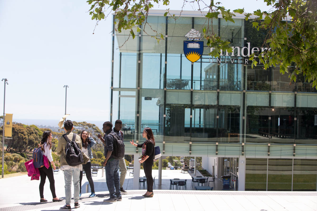 Students standing and  chatting in the sunshine outside the Flinders University student center