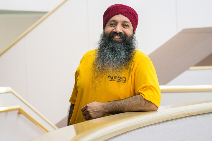 Smiling photo of Holly Singh, Senior Director of International Students & Scholars Center at Arizona State University, wearing a yellow ASU t-shirt and maroon Sikh turban
