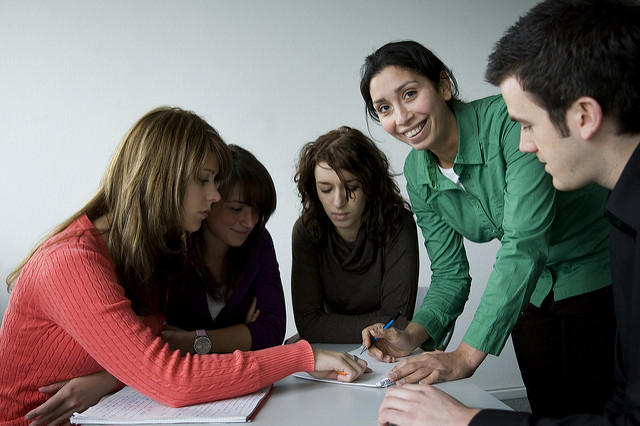 Mixed group of university students huddled over notes, with one of them looking directly at the camera and smiling