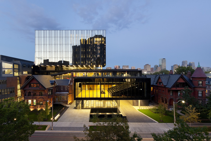 View of the Rotman School of Management building under a twilight sky, with lights glowing in the windows