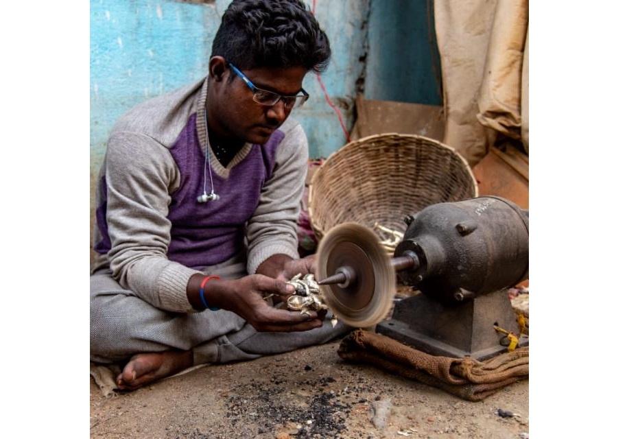 Artisan Somnath Karmakar polishing a Dhokra artefact