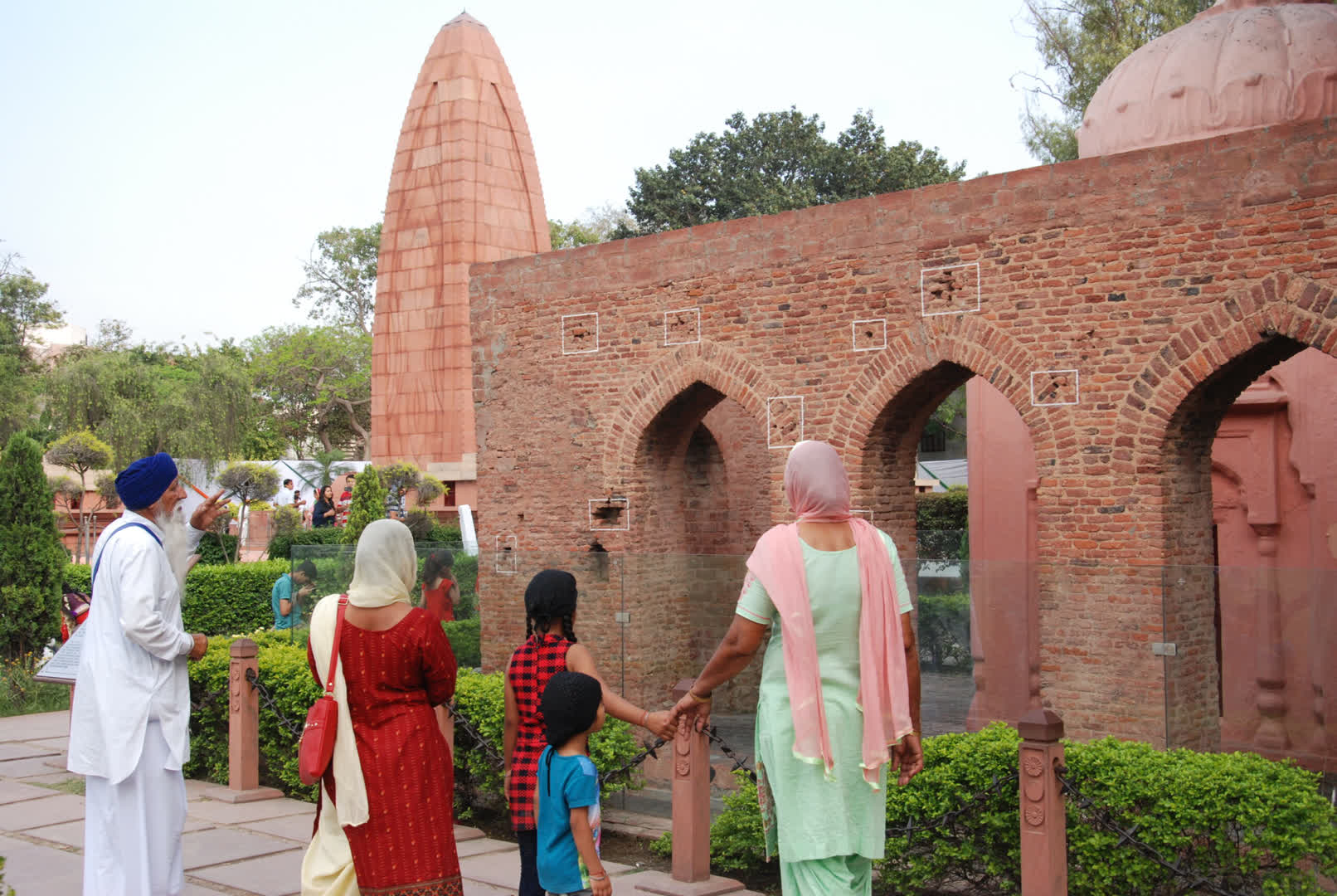 The walls marked with bullet marks in the Jallianwala Bagh, with the memorial in the backdrop