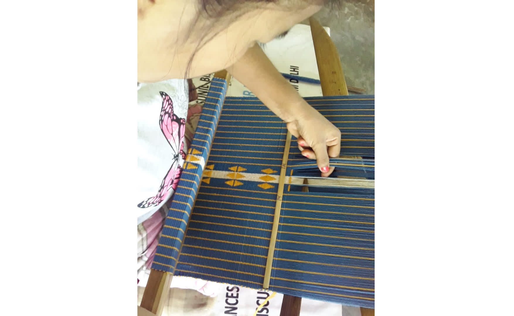 Picking up the warp yarn as per the motifs and inserting the weft