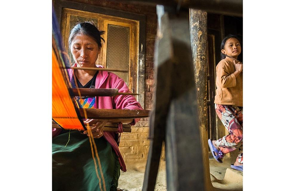 A woman weaving on loin loom