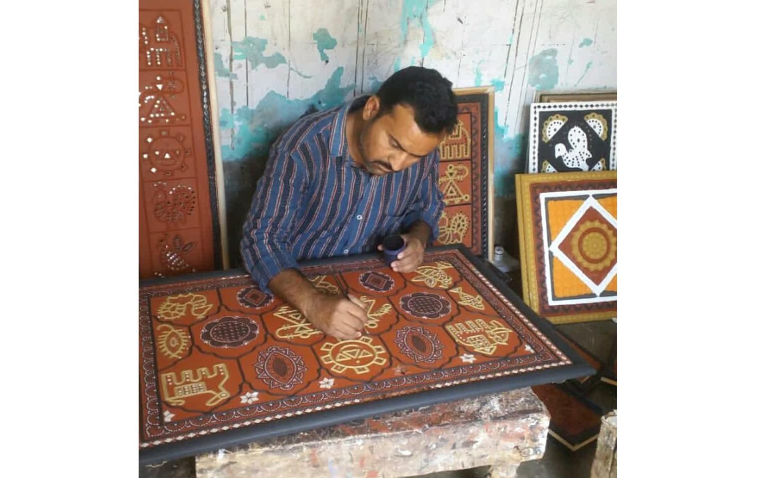 An artisan working on the Lippan art work