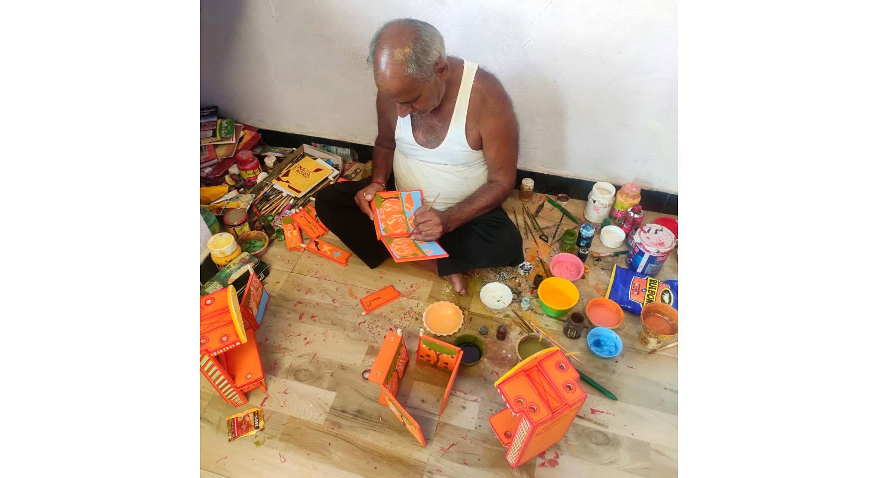 Artist Dwarka Prasad Jangid painting the wooden panels