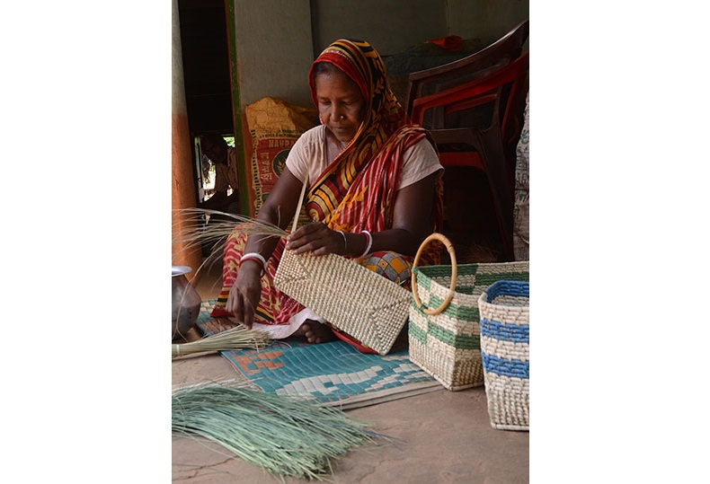 A woman crafting products from Sabai Grass