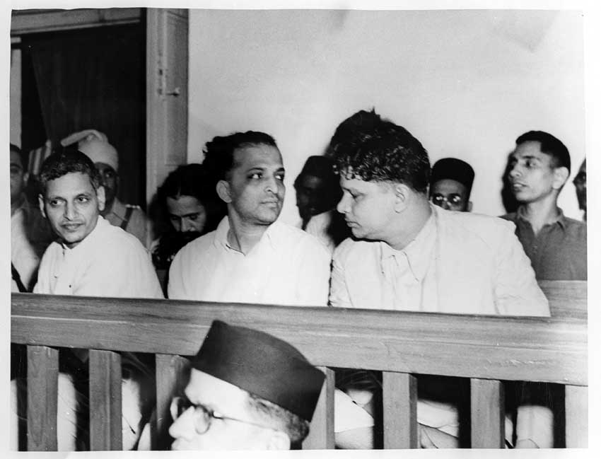 The trial of persons accused of participation and complicity in the assassination at the Special Court in Red Fort Delhi on 27 May 1948. Front row, left to right: Nathuram Godse, Narayan Apte, and Vishnu Ramkrishna Karkare. Seated behind, left to right: Digambar Badge, Shankar Kistaiya, Veer Savarkar, Gopal Godse, and Dattatraya Sadashiv Parachure.