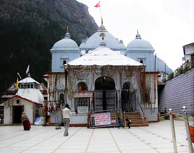 Man walking toward gangotri temple and kids are playing in the gangotri temple premis