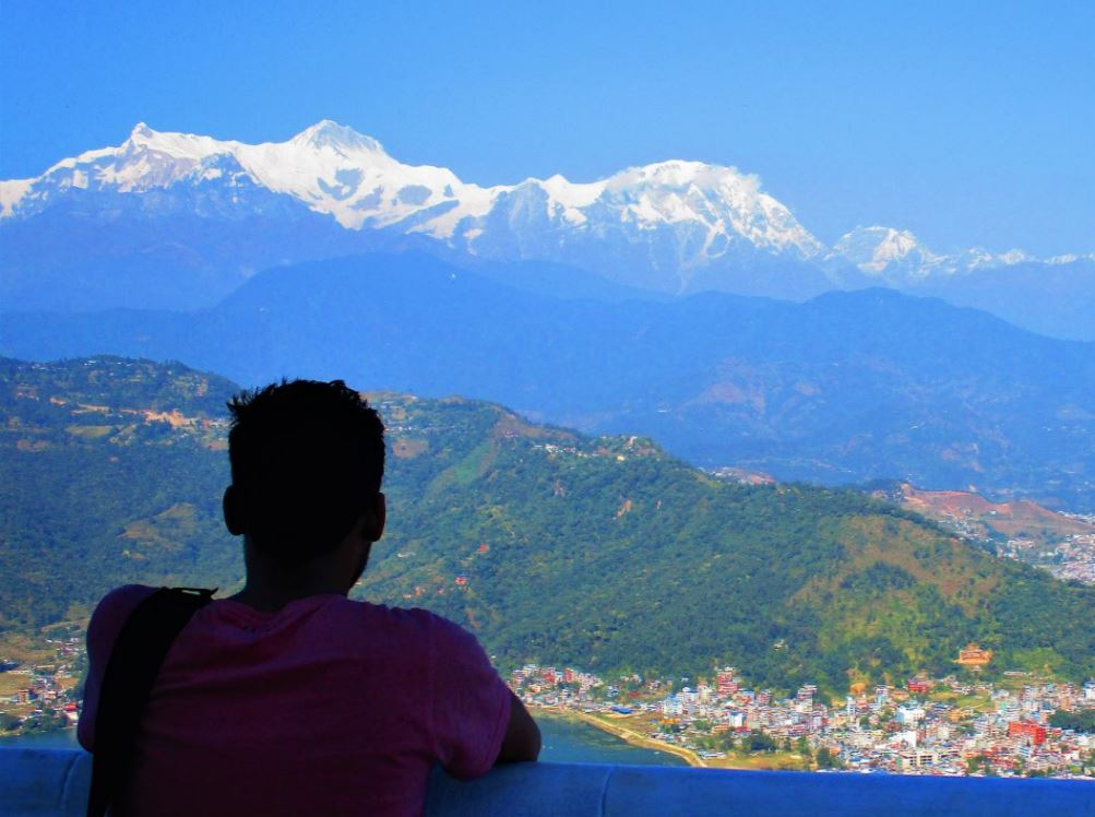 Man standing at edge looking at the snow covered mountains peak of himalayan region with local village at the foot of green mountain