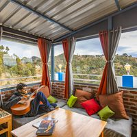 Backpacker relaxing with a guitar in common area of Zostel Mukteshwar